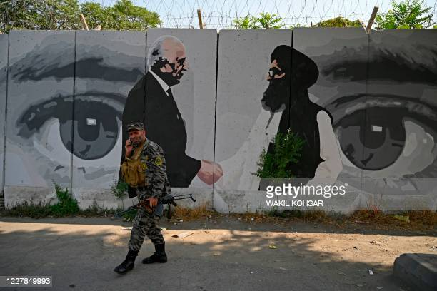Security personnel walks past a wall mural with images of US Special Representative for Afghanistan Reconciliation Zalmay Khalilzad and Taliban...