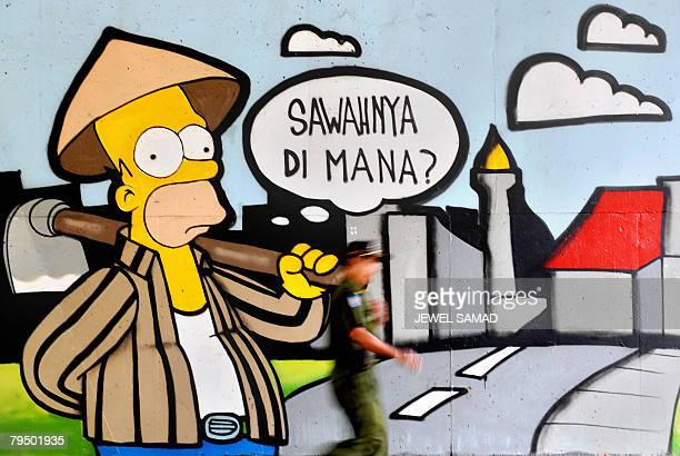 A security personnel walks past a wall painted with the cartoon character Homer Simpson and a bubble reading where is the factory in downtown Jakarta...
