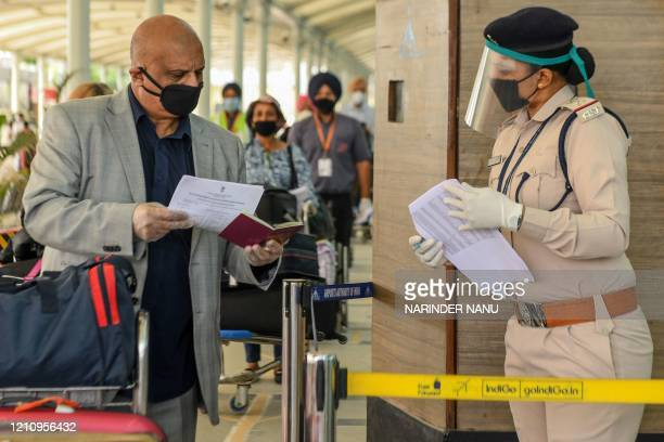 Security personnel wearing a face shield checks the passport of a British national before check-in for a special flight to London during a...
