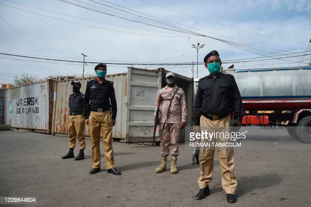 Security personnel wearing facemasks stand guard beside containers which authorities sealed after some people tested positive for coronavirus, during...