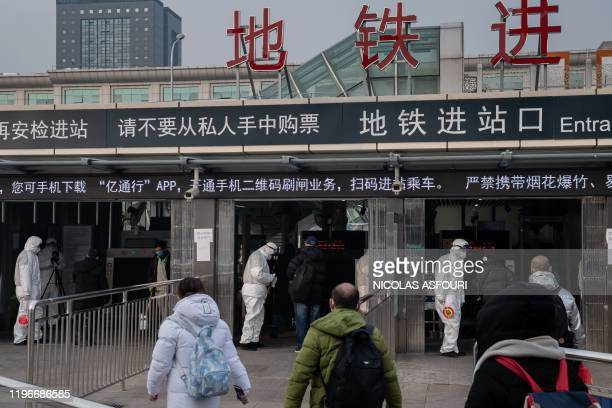 Security personnel wearing protective clothing to help stop the spread of a deadly virus which began in Wuhan check the temperature of people using...