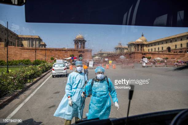 Security personnel wearing protective suits and masks spray disinfectant towards the windshield of a bus outside the South Block of the Central...