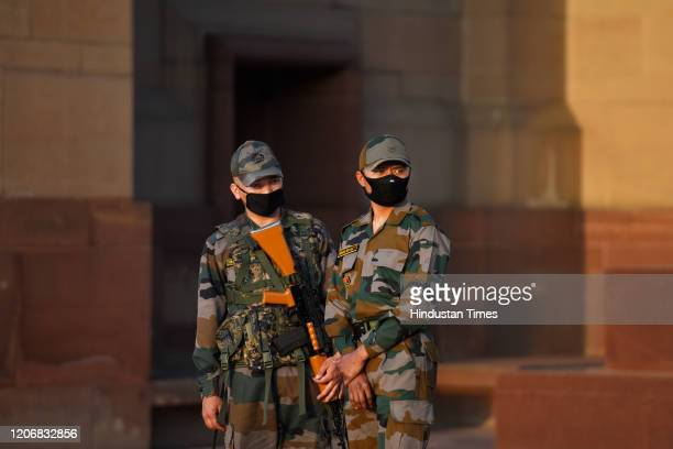 Security personnel with their faces covered with protective masks stand guard at India Gate monument as India suspended all tourist visas until April...