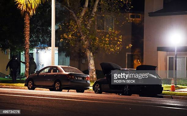 Security personnel work in the early morning hours of December 3 2015 searching a Redlands California neighborhood where a home linked to suspects in...