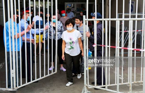 Security persons and a police officer open the gates to let shoppers leave a market in Almaty on April 25 amid the coronavirus pandemic