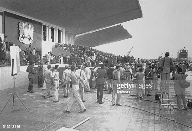 Security police and troops rush to the tarmac where President Anwar Sadat was seated watching the October 6th parade seconds after he was shot and...