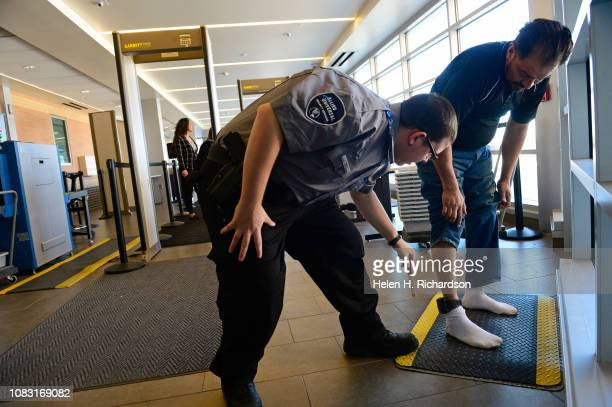 Security professional Christian McNeal left uses a tongue depressor to check for contraband inside an ankle monitor as a man goes through security...