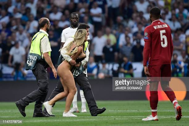 Security runs after a pitch invader during the UEFA Champions League final football match between Liverpool and Tottenham Hotspur at the Wanda...
