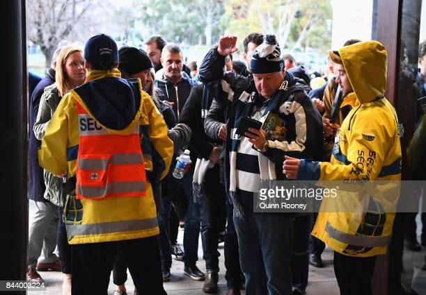 Security scan patrons as they enter the MCG during the AFL Second Qualifying Final Match between the Geelong Cats and the Richmond Tigers at...