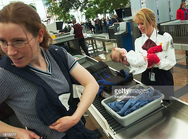 Security screener Sharon Champion holds sixmonthold Miriam Noffsinger while her mother Emily collects her belongings from a Xray machine at Denver...