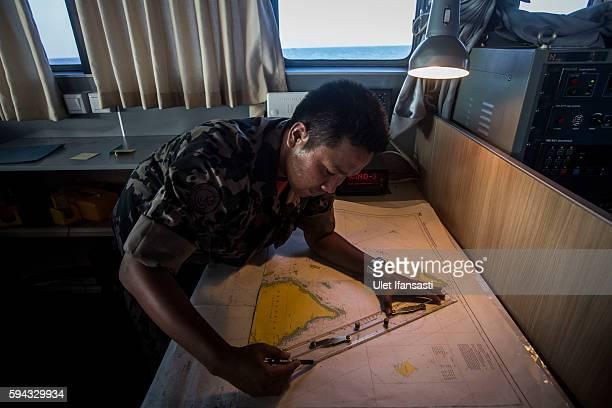 A security ship crew of Ministry of Maritime Affairs and Fisheries works on a map during a patrol in the South China Sea on August 17 2016 in Natuna...