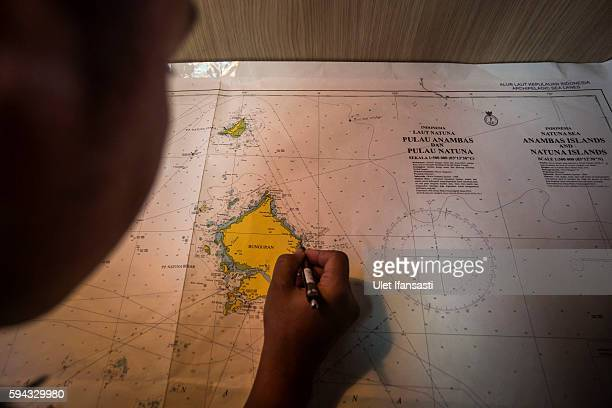 A security ship crew of Ministry of Maritime Affairs and Fisheries works on the map during a patrol in the South China Sea on August 17 2016 in...
