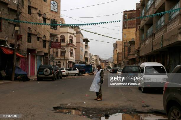 Security soldier wears a protective face mask while guarding an area which is under a 24-hour curfew imposed by Sana'a's authorities to fight the...