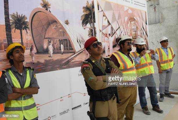 Security staff and workers stand in front of a giant poster on May 4 2016 at a construction site of a section of the Saudi capital Riyadh's $225...