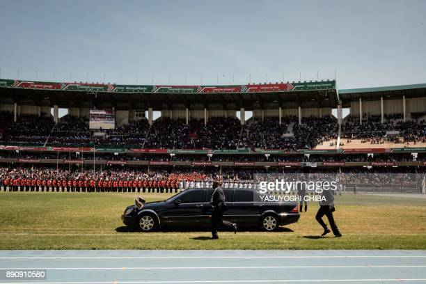 Security staff follow the car of Kenya's first lady Margaret Kenyatta upon her arrival to the Independence Day ceremony called Jamhuri Day at...
