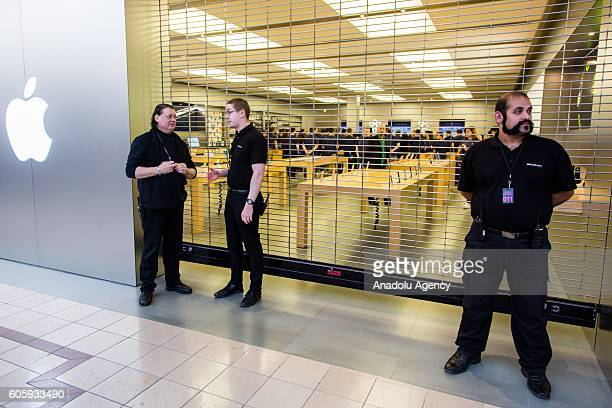 Security staff guard the entrance before the doors open while large crowds awaiting in the queue for the release of iPhone's new models in front of...