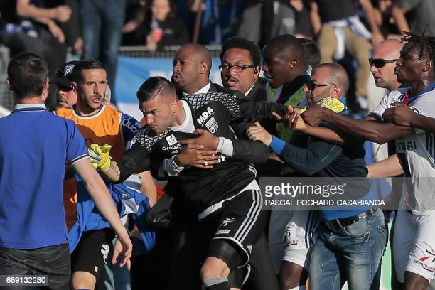 A security staff holds Lyon's goalkeeper Anthony Lopes during scuffles at halftime between some of Lyon's players and Bastia supporters who invaded...