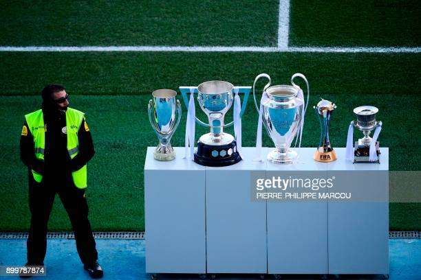 TOPSHOT A security staff member stands guard next to the trophies of the UEFA Super Cup the Spanish League the UEFA Champions League the FIFA Club...