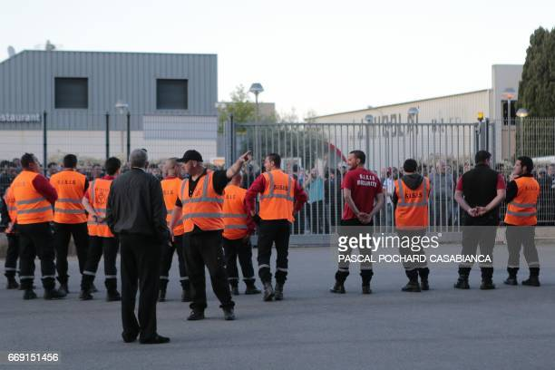 Security staff members face hundreds of Bastia's supporters waiting outside for the Lyon's bus to go out after the French L1 football match Bastia vs...