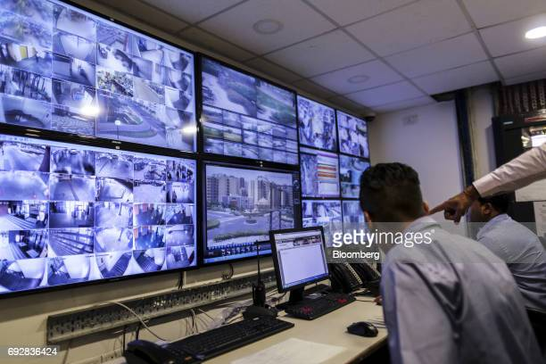 Security staff monitor screens showing closed circuit television camera footage in Palava City on the outskirts of Mumbai India on Thursday May 25...