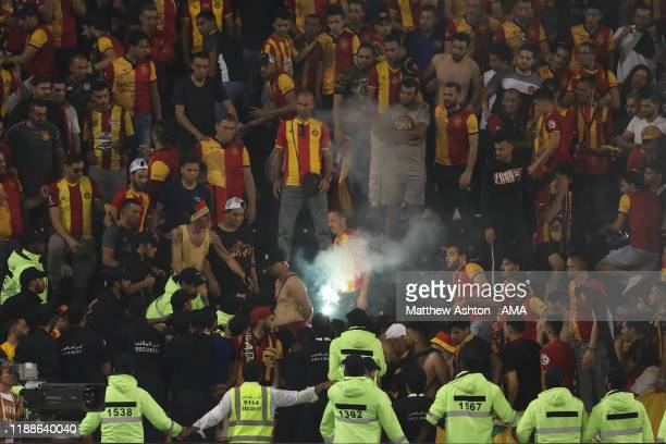 Security staff remove flares from the Esperance Sportive de Tunis fans area during the FIFA Club World Cup 2nd round match between Al Hilal and...