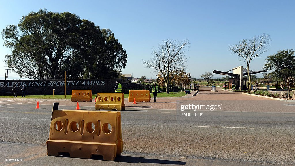 Security staff stand past the entrance to the Bafokeng Sports Campus near Rustenburg, on June 2, 2010 on the eve of the English football team arrives to stay and train ahead of their opening game against USA on June 12 during 2010 Soccer World Cup.