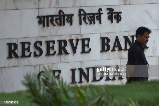 Security staff stands near an entrance of the Reserve Bank of India headquarters in Mumbai on August 7, 2019. - India's central bank on August 7 cut...