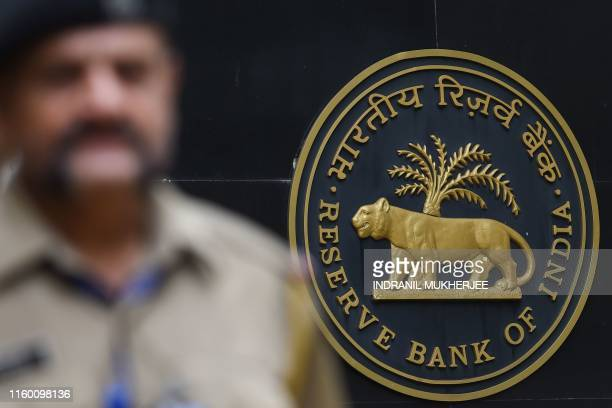 A security staff walks past the logo of Reserve Bank of India at the RBI headquarters in Mumbai on August 7 2019 India's central bank on August 7 cut...