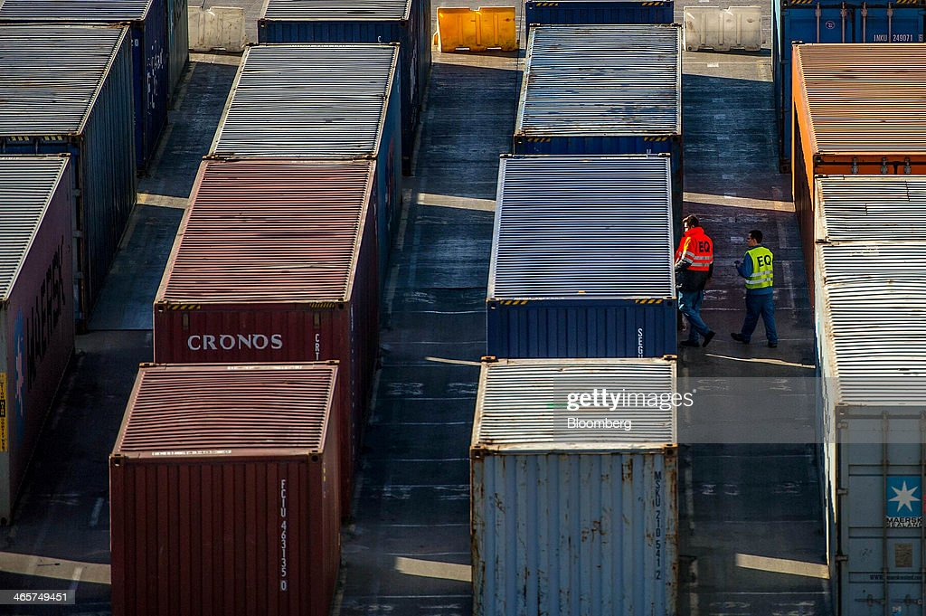 Security staff workers check shipping containers on the quayside at the commercial port in Barcelona, Spain, on Wednesday, Jan. 29, 2014. Government bonds in Europe's most-indebted countries rallied in the first three weeks of the year on signs the debt crisis that pushed those nations' borrowing costs to euro-era records had abated. Photographer: David Ramos/Bloomberg via Getty Images