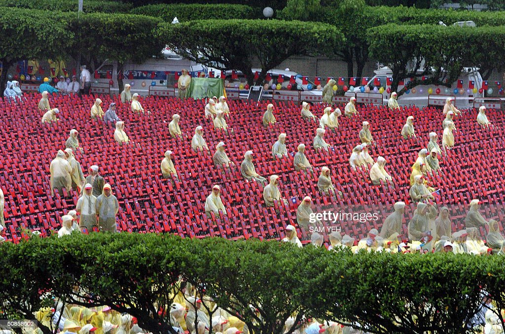 Security staffs guard empty seats prior to the inauguration ceremony in front of Presidential Palace in Taipei 20 May 2004. Taiwan's President Chen Shui-bian refused to rule out eventual reunification with China, after Beijing threatened to crush any moves by the island towards independence. AFP PHOTO/Sam YEH