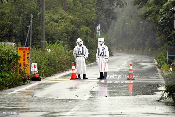 Security staffs stand in the rain to block a road leading to the nogo zone of the crippled Fukushima Daiichi Nuclear Power Plant as the Typhoon...