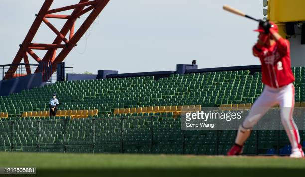 Security stand at the empty court with mask while Outfielder Tien Hsin Kuo of Wei Chuan Dragons hitting during the CPBL preseason game between CTBC...