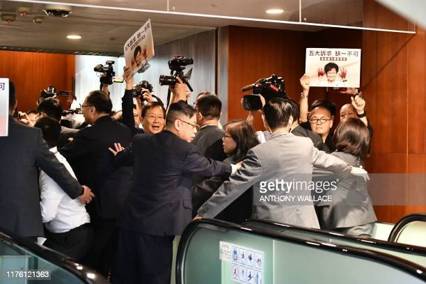 Security tries to control members of the press and protesting pro-democracy lawmakers after Hong Kong's Chief Executive Carrie Lam had to leave the...