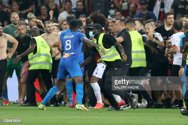 Security try to prevent fans as they invade the pitch during the French L1 football match between OGC Nice and Olympique de Marseille at the Allianz...