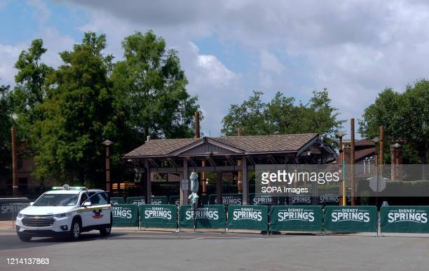 A security vehicle and barricades are seen at the closed entrance to Disney Springs at Walt Disney World a day before the retail dining and...