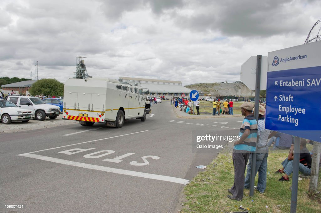 A security vehicle monitors the striking miners outside the Khomanani Mine on January 16, 2013 in Rustenburg, South Africa. Anglo American Platinum workers are refusing to work after the company announced that 14,000 jobs could be lost during a major restructuring of the company.