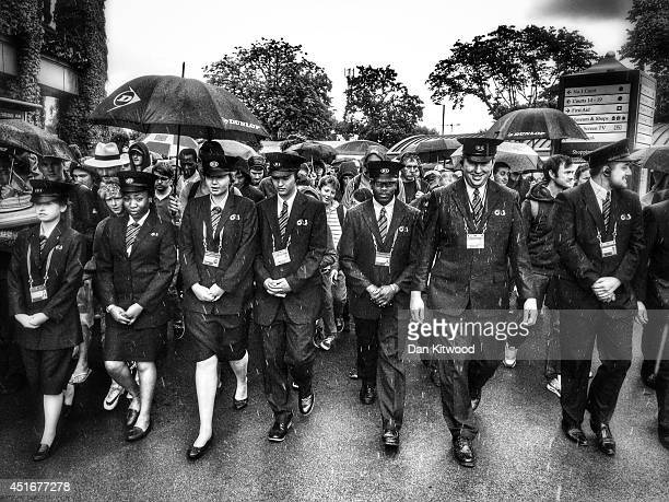 G4 Security walk members of the public into the grounds as the gates are opened during the Wimbledon Championships at the 'All England Lawn Tennis...