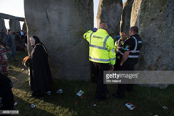 Security watch as people take part in the summer solstice dawn celebrations after druids pagans and revellers gathered for the Summer Solstice...