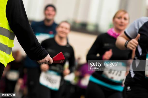 A security woman encourages with a bell the athletes running during the 12th Airport Night Run at Berlin Brandenburg Airport in Schoenefeld Germany...