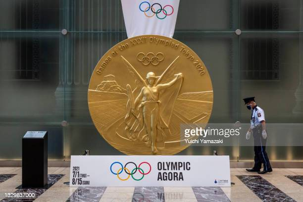Security worker checks around an Olympics gold medal monument on July 20, 2021 in Tokyo, Japan. With the Olympics now just a few days away, Tokyo is...
