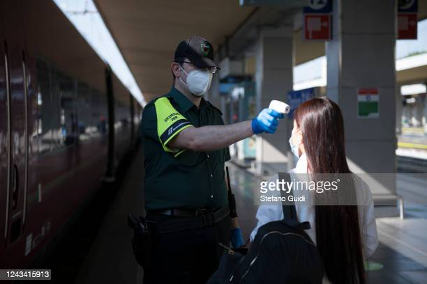 A security worker wearing a protective mask checks the body temperature of a traveler at the Porta Nuova railway station on June 03 2020 in Turin...