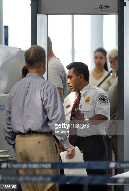A security worker with the Transportation Security Administration mans a metal detector September 10 2002 in Terminal 1 at O'Hare International...