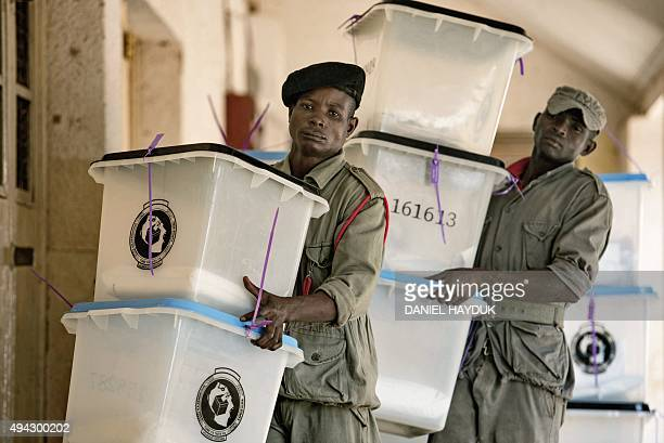 Security workers carry ballot boxes at a polling station in Dar es Salaam on October 26 2015 Votes are being counted in what is expected to be...