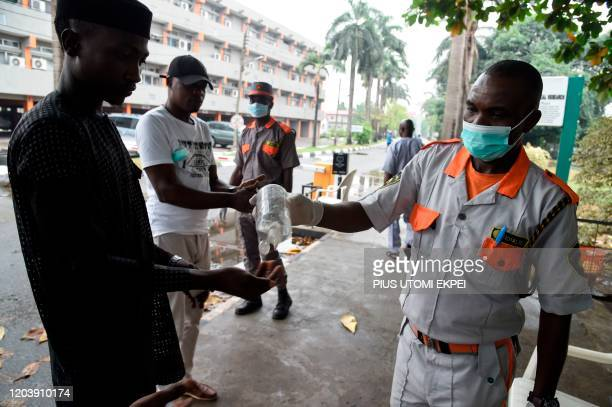 Securityman administers sanitiser to a visitor to a state hospital in Lagos, on February 28, 2020. - Residents of Nigeria's economic hub Lagos...
