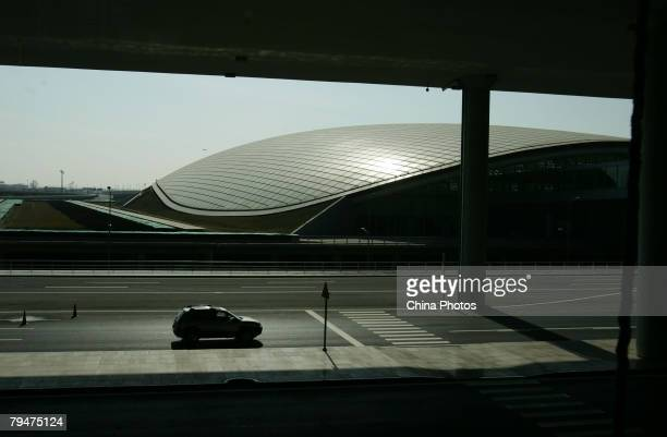 A sedan parks in front of the Ground Transportation Center connecting the Beijing airport light rail line in the new terminal building T3 at the...