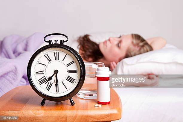 sedatives and woman lying awake in bed - insomnia - tijdmeter stockfoto's en -beelden