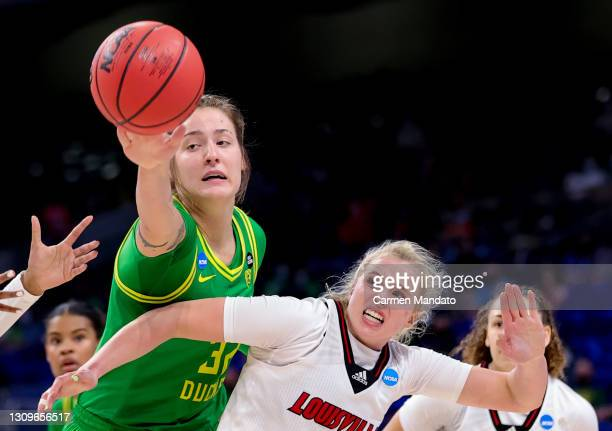 Sedona Prince of the Oregon Ducks and Hailey Van Lith of the Louisville Cardinals battle for a loose ball during the first half in the Sweet Sixteen...