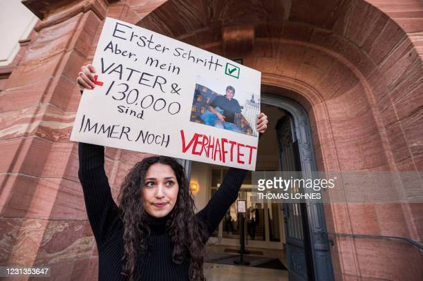Sedra Alshehabi stands with a placard with the picture of her father Ali and a text reading 'First step but my father and 130000 are still in jail'...