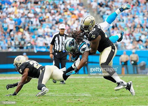 Sedrick Ellis of the New Orleans Saints tackles DeAngelo Williams of the Carolina Panthers during play at Bank of America Stadium on September 16,...