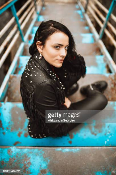 seductive goth female in leather clothing relaxing on old stairs outside - punk music stock pictures, royalty-free photos & images